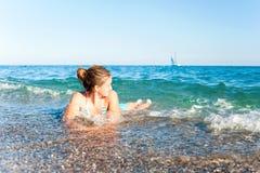 Счастливая маленькая девочка наслаждаясь в море брызгая волны среднеземноморск Стоковые Фотографии RF