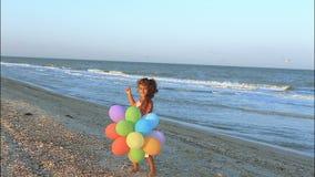 Счастливая маленькая девочка на пляже с воздушными шарами акции видеоматериалы