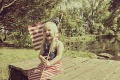 Счастливая маленькая девочка представляя с американским флагом Стоковые Фото