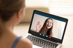 Счастливая маленькая девочка развевая к подруге от экрана компьтер-книжки Стоковое Фото