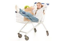 счастливая маленькая девочка сидя в магазинной тележкае и показ thumb вверх стоковая фотография
