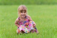 Счастливая маленькая девочка сидя в траве Стоковая Фотография RF