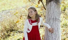 Счастливая маленькая девочка смеясь над и играя в осени на прогулке природы outdoors стоковые фото