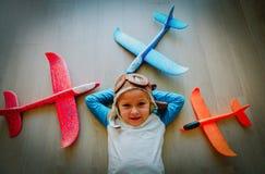 Счастливая маленькая девочка со шлемом и стекла играют с самолетами игрушки стоковое изображение rf