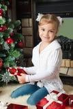 Счастливая маленькая девочка с подарками приближает к рождественской елке Стоковое Фото