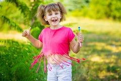 Счастливая маленькая девочка чистя ее зубы щеткой с большими пальцами руки вверх зубоврачебная гигиена стоковое фото