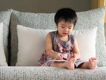 Счастливая маленькая милая девушка читает книгу на белой софе r стоковое изображение