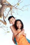 Счастливая маленькая девочка нося ее брата Стоковая Фотография