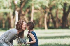 Счастливая мама и маленькая дочь сидя на лужайке в парке стоковые фото