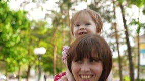 Счастливая мама носит красивую маленькую дочь на его плечах, прогулку в парке с ребенком видеоматериал