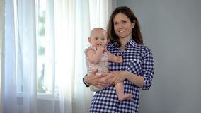 Счастливая мать держа милый ребёнок в оружиях, усмехаясь в камеру, материнство стоковое фото
