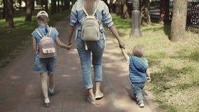 Счастливая мать держит детей рукой пока идущ в парк акции видеоматериалы