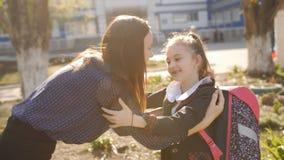 Счастливая мать ждет маленькую дочь, перво-грейдер от школы после школы Бега грейдера школьницы первые до видеоматериал