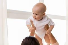 Счастливая мать играя с маленьким ребёнком дома стоковое изображение rf