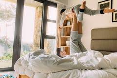 Счастливая мать играя с мальчиком на кровати стоковые изображения rf