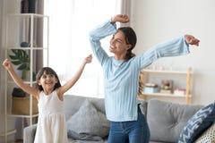Счастливая мать имеет потеху танцуя с небольшой дочерью стоковое изображение