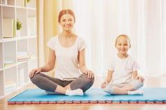 Счастливая мать и дочь делая йогу дома Стоковое Изображение