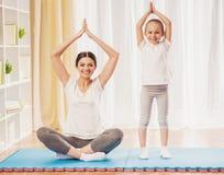 Счастливая мать и дочь делая йогу дома Стоковая Фотография RF