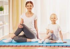 Счастливая мать и дочь делая йогу дома Стоковое Фото