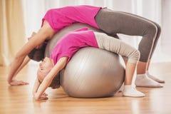 Счастливая мать и дочь делая йогу дома Стоковые Изображения RF