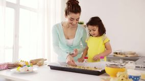 Счастливая мать и дочь делая печенья дома