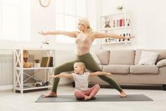 Счастливая мать и дочь имея йогу тренируя дома Стоковое фото RF