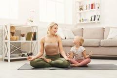 Счастливая мать и дочь имея йогу тренируя дома Стоковые Изображения
