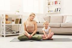 Счастливая мать и дочь имея йогу тренируя дома Стоковые Фото