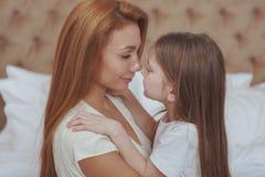 Счастливая мать и дочь отдыхая дома совместно стоковое фото