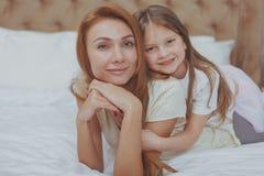 Счастливая мать и дочь отдыхая дома совместно стоковые фотографии rf