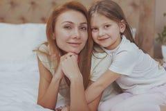 Счастливая мать и дочь отдыхая дома совместно стоковое изображение
