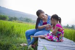 Счастливая мать и ее детская игра outdoors имея потеху, землю зеленого поля риса заднюю стоковые фотографии rf