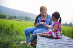 Счастливая мать и ее детская игра outdoors имея потеху, землю зеленого поля риса заднюю стоковая фотография