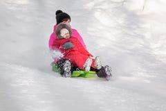 Счастливая мать и ее дочь наслаждаясь розвальнями едут вниз с высокой Стоковые Изображения RF