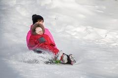 Счастливая мать и ее дочь наслаждаясь розвальнями едут вниз с hils Стоковые Фото