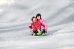 Счастливая мать и ее дочь наслаждаясь розвальнями едут вниз с hils Стоковая Фотография RF