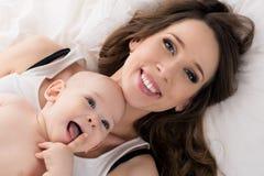 Счастливая мать и ее сын младенца лежа на кровати совместно семья счастливая мать ребенка newborn Стоковая Фотография RF