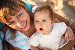 Счастливая мать и малая дочь сидя и играя совместно на пляже Стоковое фото RF