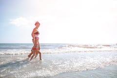 Счастливая мать и маленькая дочь бегут на пляже на заходе солнца стоковая фотография