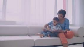 Счастливая мать и маленький сын читая книгу в утре совместно в живущей комнате дома Концепция деятельности при семьи видеоматериал