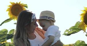 Счастливая мать и мальчик обнимая на поле с солнцецветами видеоматериал
