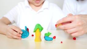 Счастливая мать и ребенок играя с диаграммами от пластилина, теста, смешивая моделей, крупного плана акции видеоматериалы