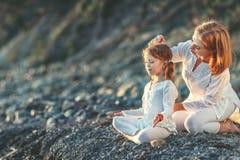 Счастливая мать и ребенок семьи делая йогу, размышляют в posi лотоса Стоковое Изображение