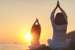 Счастливая мать и ребенок семьи делая йогу, размышляют в posi лотоса Стоковые Фотографии RF