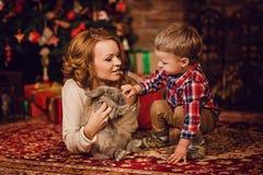 счастливая мать и сын сидя около рождественской елки и камина Стоковые Фото