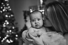 Счастливая мать обнимая дочь младенца для рождественской елки освещает на заднем плане стоковая фотография rf