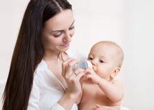 Счастливая мать подает бутылка младенца Стоковое Изображение RF