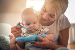 Счастливая мать при ребёнок дома давая детское питание стоковое фото rf