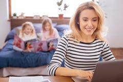 Счастливая мать работая на ее компьтер-книжке Стоковые Фотографии RF