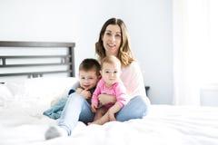 Счастливая мать семьи и 2 дет, сын и дочь в кровати Стоковое Изображение